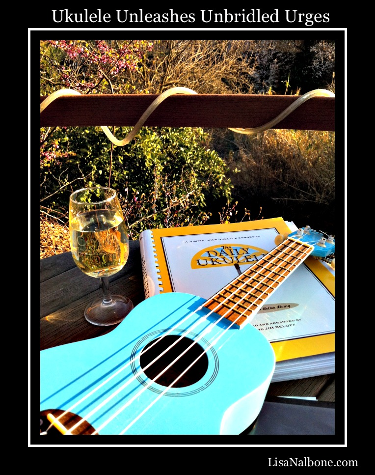Blue ukulele, glass of wine and daily ukulele music book on deck. Ukulele Unleashes Unbridled Urges by Lisa Nalbone
