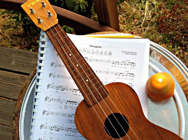 Dr. Uke says imagine, ukulele, candle and imagine by John Lennon on the deck.