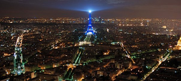 Overivew of the city of Paris at night with Eiffell Tower lit in blue.
